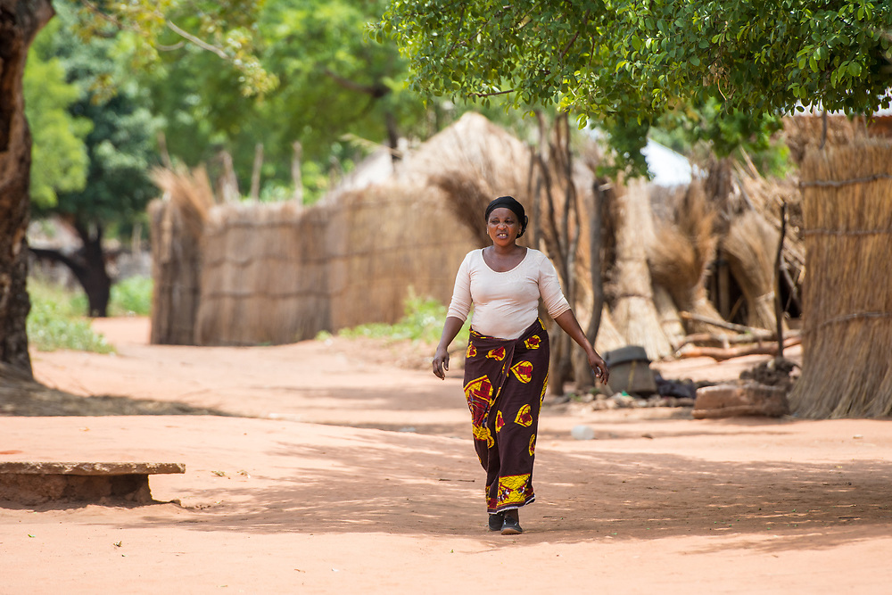 Zambian women in traditional patterned skirt walks by herself through village, Mukuni Village, Zambia