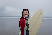 Female surfer carrying surfboard standing in shallow water