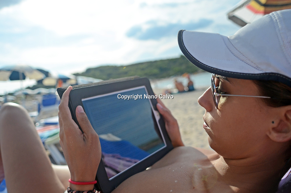 Young attractive woman using a tablet on the beach