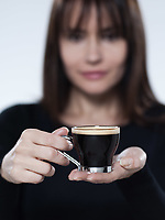 beautiful caucasian brunette drinking offering coffee on isolated background