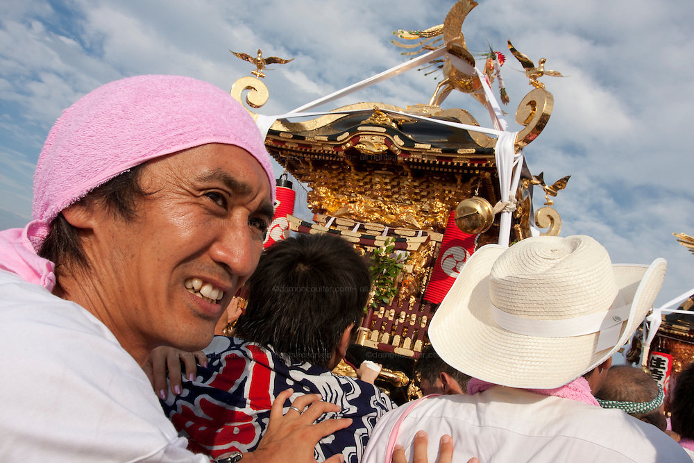 Portrait of a mikoshi supporter during the Hamaorisai Matsuri that takes place on Southern Beach in Chigasaki, near Tokyo, Kanagawa, Japan Monday July 20th 2009. The festivals marks the celebration of Marine Day and the rescuing of a divine image that was washed ashore in the area. Over thirty Mikoshi or portable shrines are carried through the night from surrounding shrines to arrive on the beach for sunrise. There they are blessed and then carried into the surf to purify them.