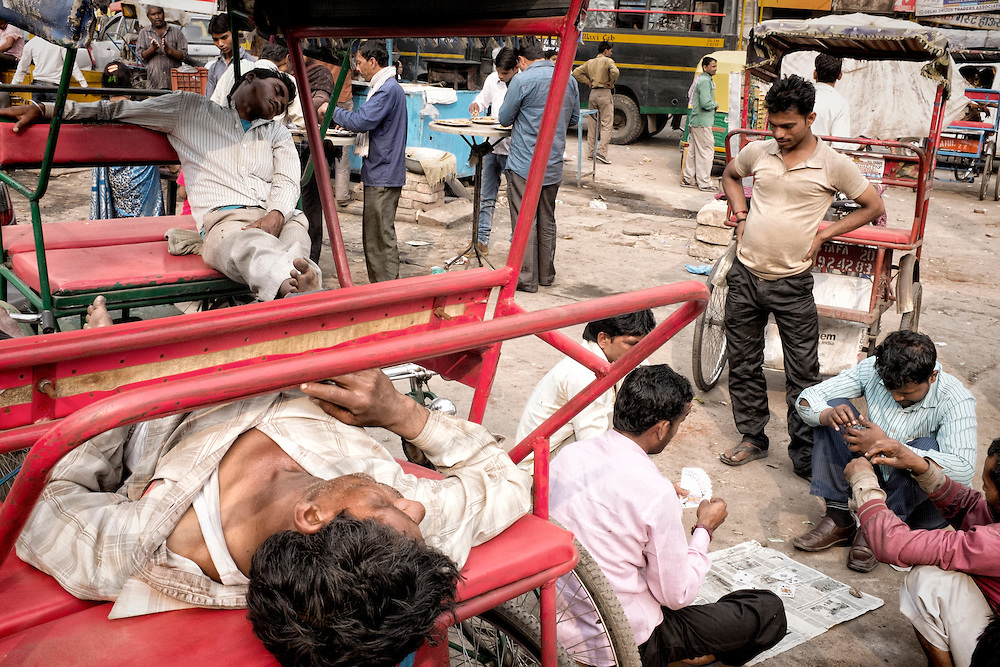 Group of men resting and playing in the streets of Old Delhi, India.