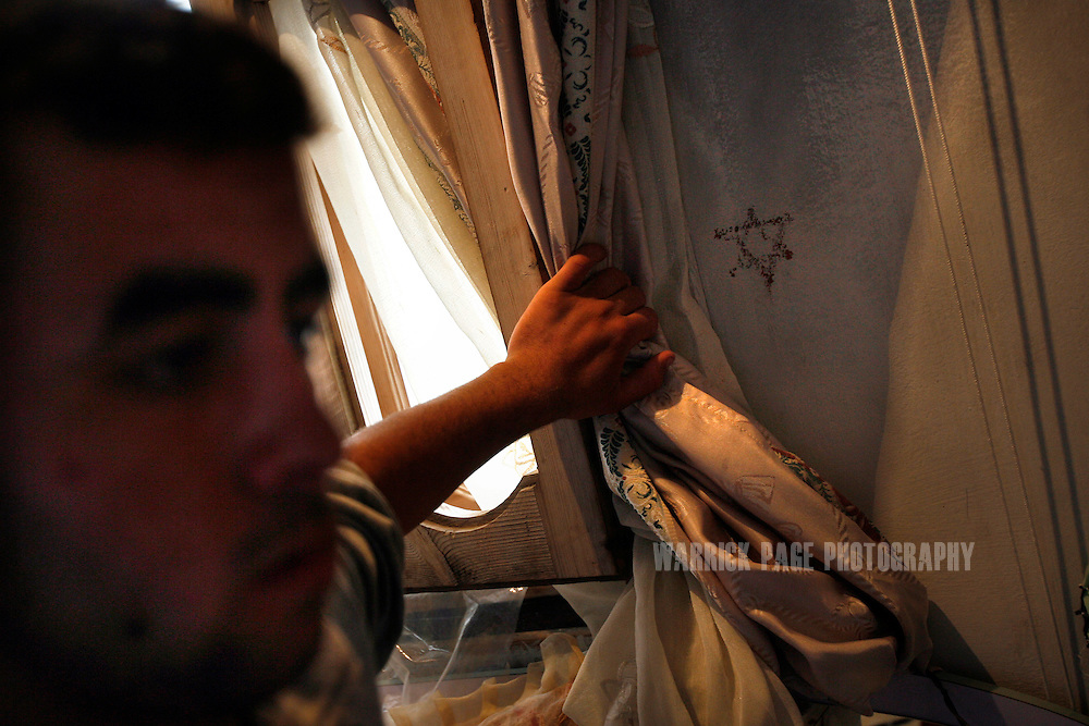 ATATRA, GAZA STRIP - JUNE 4: Omar Abu Halima shows a Star of David drawn on his parents bedroom wall by a soldier, after Israeli forces occupied his family home during the recent war in Gaza, June 4, 2009, in Atatra, Gaza Strip. The family also claimed more than $5000 went missing during the time soldiers were occupying their home. Eight members of the Abu Halima family were killed after a white phosphorus artillery strike burst through the ceiling of their home during the recent war in Gaza, while two others were shot dead while trying to evacuate the wounded. Not since Fallujah or Grozny has white phosphorus been used so extensively in a civilian area. Phosphorus shells are legal to use as a battlefield obscurant in unpopulated areas, but are banned from use under the UN's Convention on Conventional Weapons (CCW) where civilians may be harmed. (Photo by Warrick Page)
