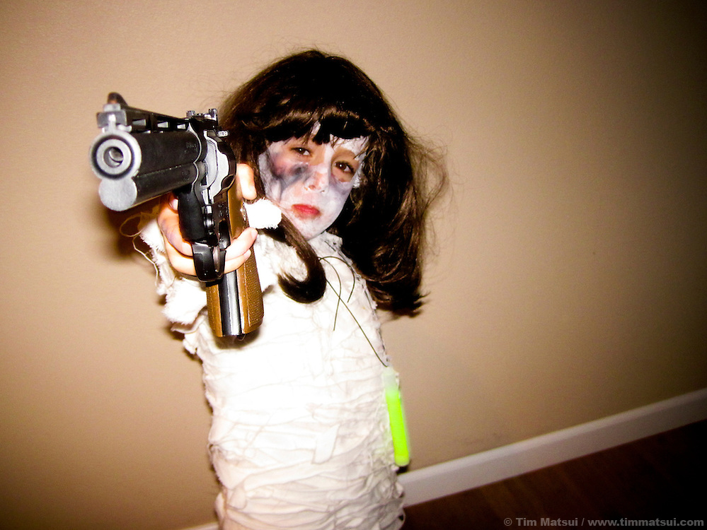 A six year old boy in a halloween costume with a wig and a hand gun pointed at the camera.
