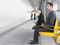 Businesspeople sitting on benches Waiting at Train Station side view