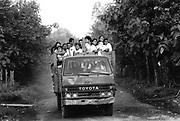 School children arrive at school in a pick-up truck. Community of Nueva Esperanza, El Salvador, 1999.