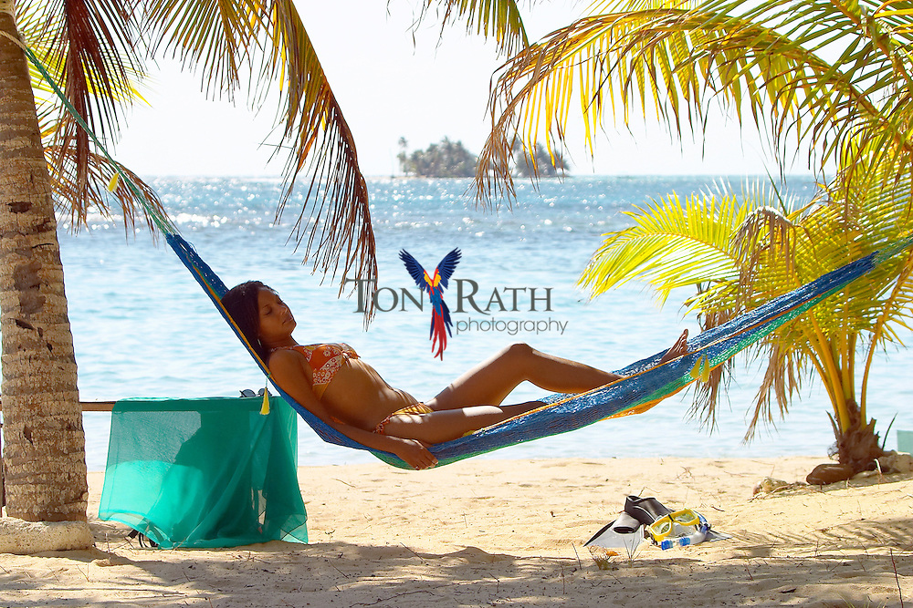 Young woman relaxes in hammock on South Water Caye with distant island in the back ground, Stann Creek District, Belize