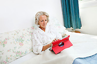 Senior woman using digital tablet on bed at home