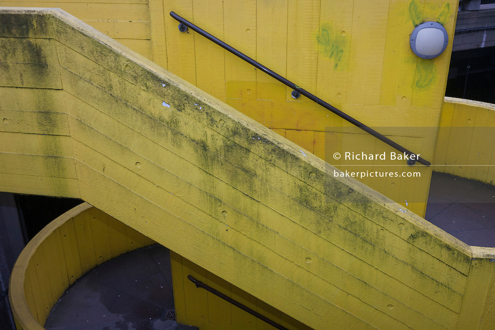 Weathered and fading yellow stairwell architecture, on 31st January 2017, in Southbank, London, England.