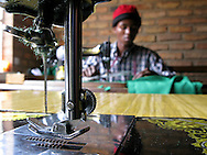 Kigali, Rwanda -A Rwandan man sews trousers using a treadle sewing machine at a business run by local church women in Kigali, Rwanda.