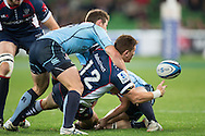 Rory Sidey (Rebels) makes an offload pass as he's tackled by Bernard Foley (Waratahs) during the Round 15 match of the 2013 Super Rugby Championship between RaboDirect Rebels vs HSBC Waratahs at AAMI Park, Melbourne, Victoria, Australia. 24/05/0213. Photo By Lucas Wroe