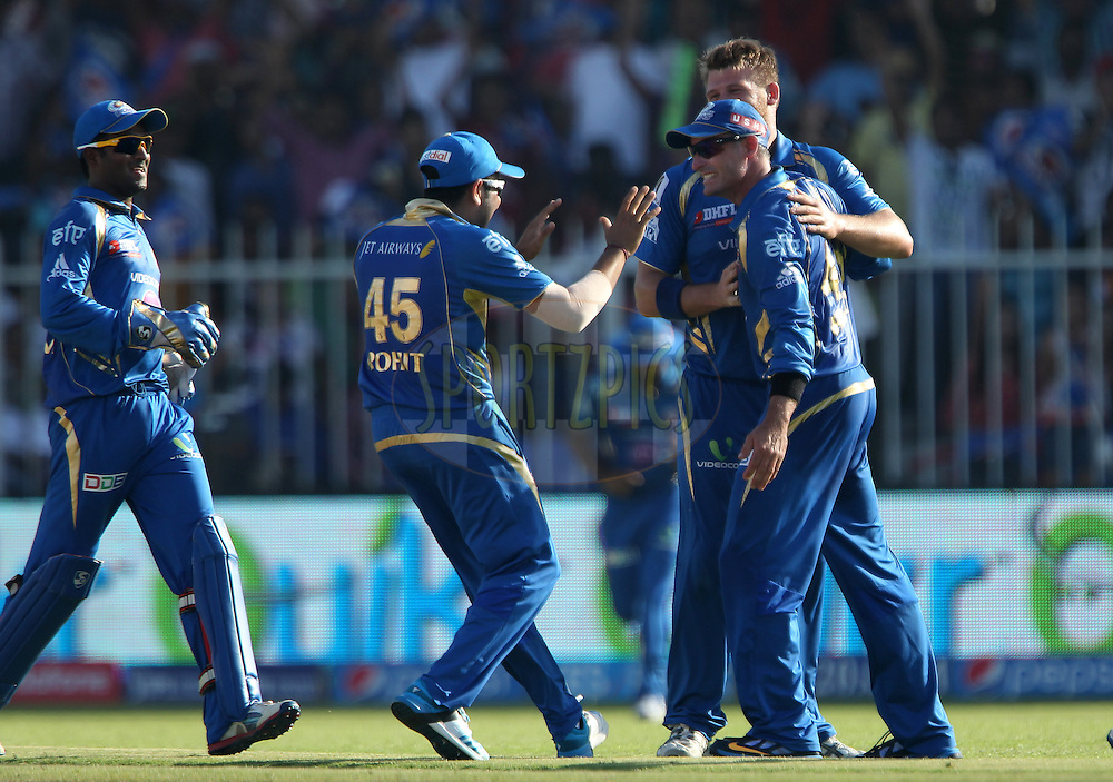 Rohit Sharma captain of of the Mumbai Indians, Corey Anderson of the Mumbai Indians  and Michael Hussey of the Mumbai Indians celebrate the wicket of Quinton de Kock of the Delhi Daredevils during match 16 of the Pepsi Indian Premier League 2014 between the Delhi Daredevils and the Mumbai Indians held at the Sharjah Cricket Stadium, Sharjah, United Arab Emirates on the 27th April 2014<br /> <br /> Photo by Ron Gaunt / IPL / SPORTZPICS