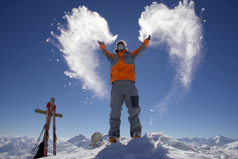 Lifestyle. Male skier throwing snow into the air in the shape of a heart, Serre Chevalier ski resort, France...