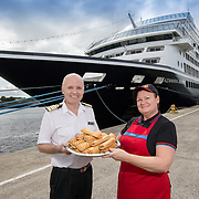 """*** FREE FOR EDITORIAL USE ***<br /> <br /> L to R : Captain Johannes Tysse and Diane, store manager from Newcastle.<br /> <br /> <br /> 19 August 2019<br /> <br /> The Captain of a luxury cruise ship, which docked at the Port of Tyne for the first time today, made an unusual order in the form of a special delivery from Greggs.<br /> <br /> Azamara Cruises offer unforgettable journeys, the luxury cruise line prides itself in offering boutique experiences. A typical cruise will require as much as 60 tonnes of food-stuffs, including the finest wine, oysters, caviar and kobe beef. On your average 10 night cruise passengers and crew will eat as many as 35,000 meals or more! As much as 120 lbs of lobster and 630 litres of ice cream may be eaten. <br /> <br /> But when the 181m long Azamara Journey dropped anchor near Newcastle upon Tyne it was missing some vital ingredients. Greggs Sausage Rolls, Vegan Sausage Rolls and North East favourite – Stottie Bread. <br /> <br /> Greggs were initially contacted by the ship's Assistant Cruise Director, Lee Hetherington from Heworth in Gateshead, who is very enthusiastic about some of Greggs' famous menu items. So much so, that Captain Johannes Tysse took the opportunity to order a boat load for the ship's 700 passengers who are visiting as part of a 10-day culinary and cultural tour of Northern Europe.<br />  <br /> The team at a local Greggs shop on Newcastle's Grainger Street were on hand in the early hours to prepare for the morning delivery which was delivered directly on to the cruise ship by Greggs employees in partnership with the Port of Tyne. <br />  <br /> Norwegian Captain Johannes Tysse of Azamara, said: """"On our cruise of Northern Europe passengers will enjoy amazing dining experiences including visits to Bruges and Amsterdam. Our UK crew told us that a visit to Newcastle wouldn't be complete without a taste of Greggs as a culinary 'must-try', and that for European travellers it joins the echelons of British food icons"""