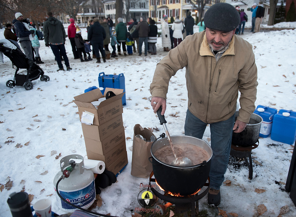 """BRUNSWICK, Maine  11/24/18 -- Mark Rockwood of Brunswick, stirs the hot chocolate at the Brunswick's tree lighting event on Saturday. He said, """"No weak cocoa here,"""" as added three cans to the batch. Hannaford supermarket donated the cocoa. <br /> Trevor Geiger, of Brunswick Downtown Association, said that the organization expected over 1500 guests at the event and that they counted participation by the number of cups of cocoa they passed out. He added that there were more than 20 volunteers helping out with the event and over 1500 cookies were on the table. Most were homemade, by volunteers. Photo by Roger S. Duncan."""