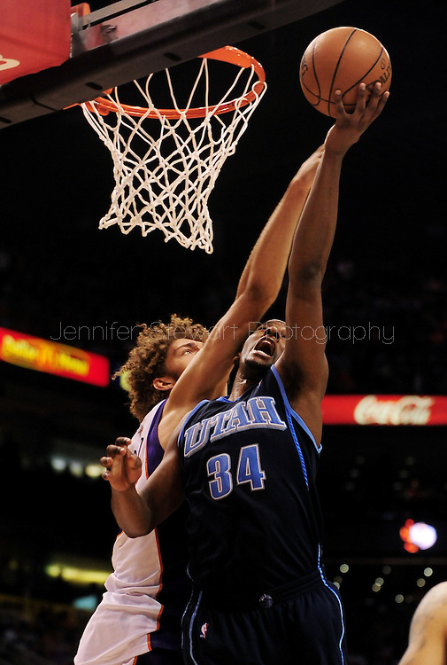 Mar. 19 2010; Phoenix, AZ, USA; Utah Jazz forward C.J. Miles (34) puts up a shot against Phoenix Suns center Robin Lopez (15) in the second half at the US Airways Center.  The Suns defeated the Jazz 110-100. Mandatory Credit: Jennifer Stewart-US PRESSWIRE.