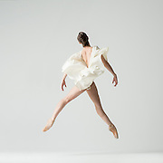 Contemporary female dancer, Jessica Miller, photographed in the photo studio in a white dress against a white background. Photograph taken in New York City by photographer Rachel Neville.