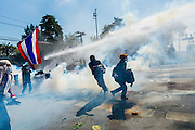 01 DECEMBER 2013 - BANGKOK, THAILAND: Thai anti-government protestors run through a cloud of tear gas in Bangkok. Thousands of anti-government Thais confronted riot police at Phanitchayakan Intersection, where Rama V and Phitsanoluk Roads intersect, next to Government House (the office of the Prime Minister). Protestors threw rocks, cherry bombs, small explosives and Molotov cocktails at police who responded with waves of tear gas and chemical dispersal weapons. At least four people were killed at a university in suburban Bangkok when gangs of pro-government and anti-government demonstrators clashed. This is the most serious political violence in Thailand since 2010.    PHOTO BY JACK KURTZ