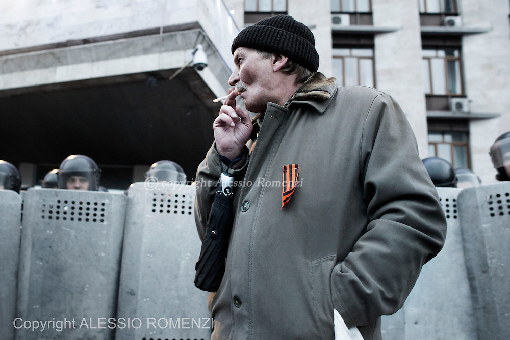 Ukraine, Donetsk: A pro-Russia demonstrator is seen in front of the Regional Parliament building graded by Ukrainian riot police during a rally in Donetsk on March 16, 2014. Pro-Russia demonstrators in the eastern city of Donetsk called Sunday for a referendum similar to the one in Crimea as some of them stormed the prosecutor-general's office. ALESSIO ROMENZI