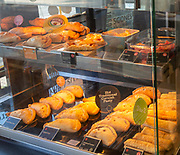 Hot pies and traditional pasty in display cabinet inside bakery shop, UK