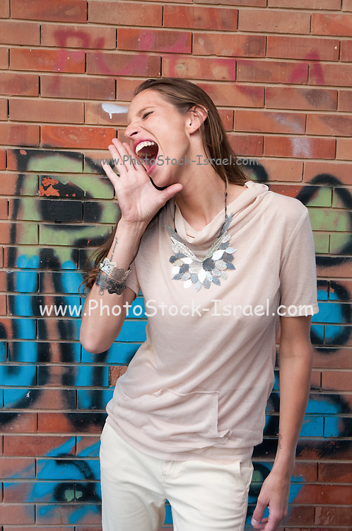 A hip and trendy young woman shout in front of a brick wall with graffiti Model release available