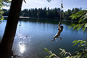 Andrew Elliott, 18, of Issaquah, Wash, scoots out over the water before letting go of a rope swing Wednesday, Aug. 13, 2008, at Echo Lake near North Bend, Wash. Elliott came to the lake with two other friends after enduring the heat earlier in the day.