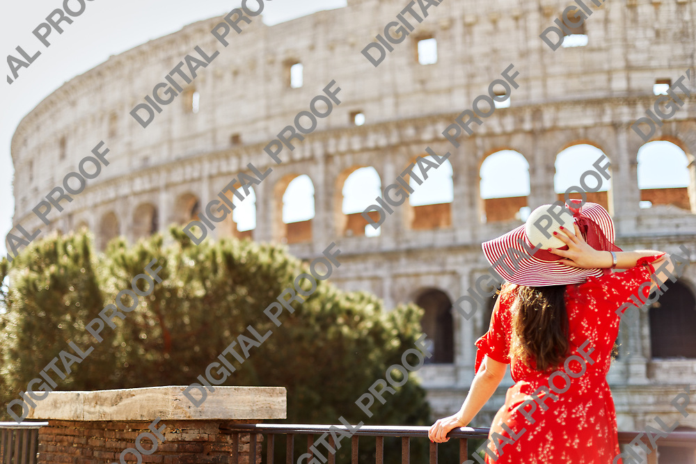 Standing vintage girl wears a red dress and hat while looking and admiring the colosseum