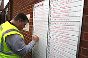 A steward adds the team line ups to the whiteboard before the FA Trophy match between Whitehawk FC and Dover Athletic at the Enclosed Ground, Whitehawk, United Kingdom on 12 December 2015. Photo by Bennett Dean.