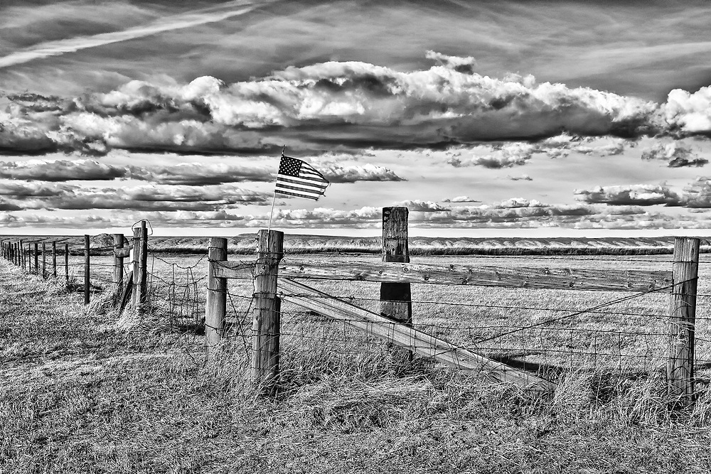 Old Glory whipping in the wind atop a rural Wyoming fence rail.
