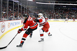 Oct 17, 2009; Newark, NJ, USA; Carolina Hurricanes right wing Tom Kostopoulos (29) hits New Jersey Devils defenseman Paul Martin (7) during the first period at the Prudential Center.