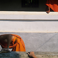 Asia, Laos, Luang Prabang, Young monks scrape paint from walls at Wat Sop Buddhist Temple in early morning