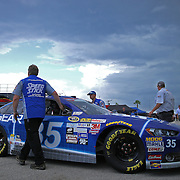 Crew members for Sprint Cup driver Cole Whitt move his car as bad weather moves into the are prior to the 57th Annual NASCAR Coke Zero 400 stock car race at Daytona International Speedway on Sunday, July 5, 2015 in Daytona Beach, Florida.  (AP Photo/Alex Menendez)