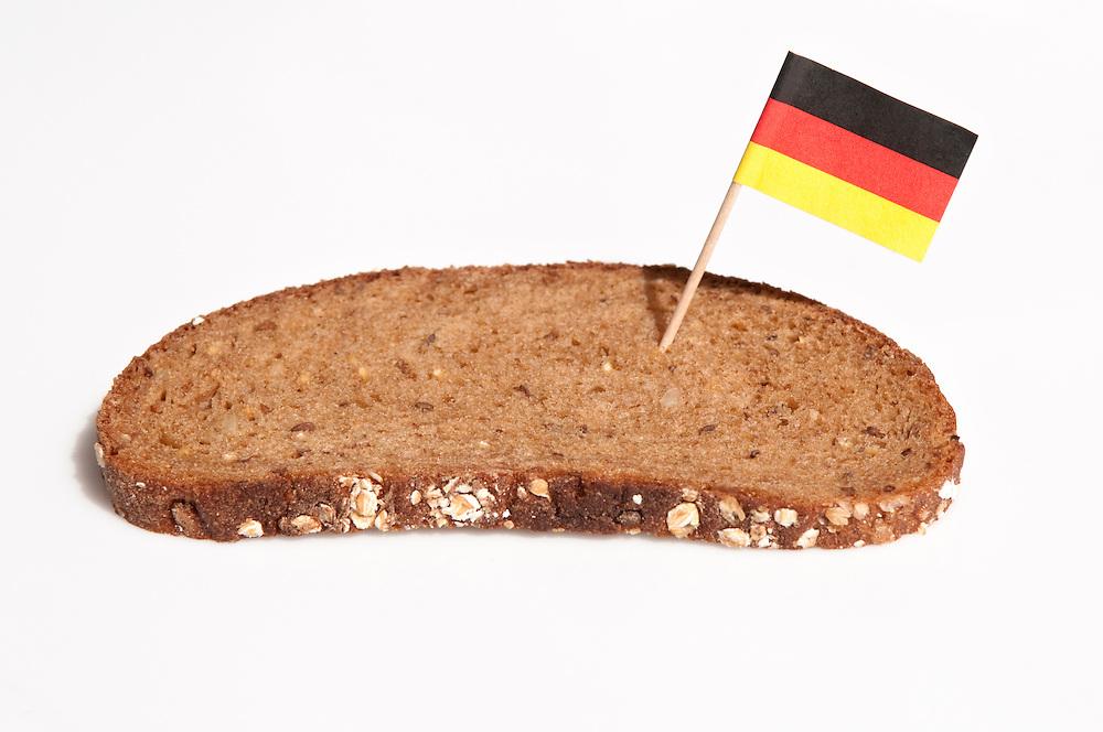 Schwarzbrot mit Deutschlandfaehnchen|  dark German bread with German flag        |