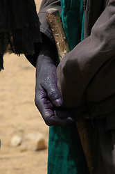 BURKINA FASO, Gorom-Gorom, 2007. Hands stained purple by home turban dying, this Tuareg is buying cattle at Gorom-Gorom's Thursday market, famous in the region.