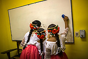 Paraguayan girls dressed in folkloric costumes play on a board writing the name of their dance school, Yasi, in Guarani (the word means moon) in Asuncion, Paraguay, Thursday, Dec. 14, 2017. Paraguay today is trying to promote a positive image of Guaraní language but bilingual education programme is under resourced and has failed to reach many areas of rural or impoverished parts of Paraguay, where Guaraní speakers are still schooled through Spanish, leading many to drop out. Part of the issue is that the language taught in schools is not that of the streets, with teachers tending to be puritanical and teaching words that have long since fallen out of use. (Dado Galdieri for The New York Times)