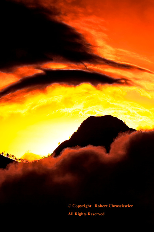 Volcanic Sunset: A volcanic silhouette is cast below a sky seemingly set on fire, as the evening mist gathers below, near Mentagi Lombok Indonesia.