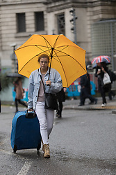© Licensed to London News Pictures. 28/03/2018. London, UK. A woman with a suitcase walks from Waterloo Station during rain and wet weather this morning. Photo credit: Vickie Flores/LNP