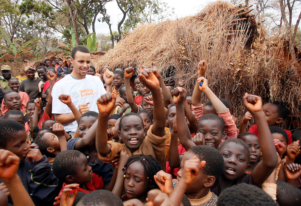 NBA superstar Stephen Curry celebrates the arrival of mosquito nets with children in the Nyarugusu Refugee Camp in Tanzania, during a Nothing But Nets trip to distribute anti-malaria bed nets, Tuesday, July 30, 2013. (Insider Images/Stuart Ramson for UN Foundation)