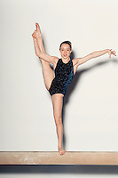 Gymnast (13-15) stretching one leg in air on balance beam portrait