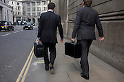 Two city businessmen walk along a financial district street each carrying identical briefcases.