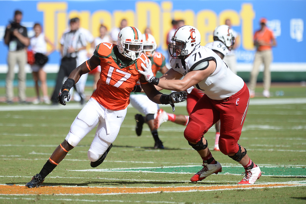 October 11, 2014: Eric Lefeld #71 of the Cincinnati Bearcats looks to block Tyriq McCord #17 of the Miami Hurricanes during the football game between the Cincinnati Bearcats and the Miami Hurricanes at Sun Life Stadium in Miami Gardens, FL. The Hurricanes defeated the Bearcats 55-34.