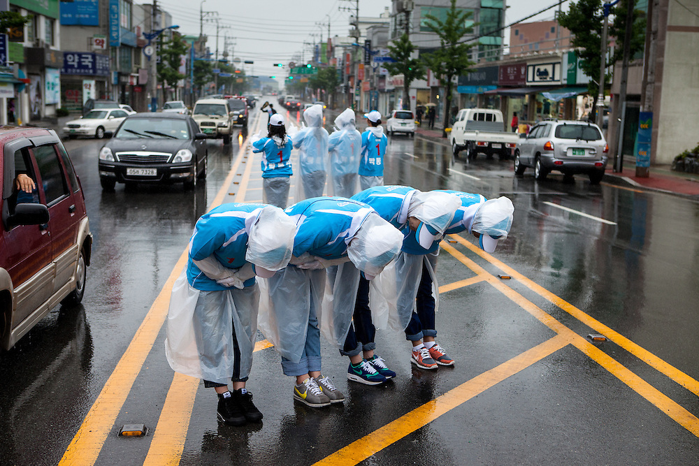 A group of young students working as election helpers in the middle of the main road of Gwangyang bowing in front of every car that passes to show their respect. The students are  earning a little spare money from campaigning.