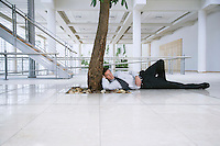 Businessman sleeping under tree outside office