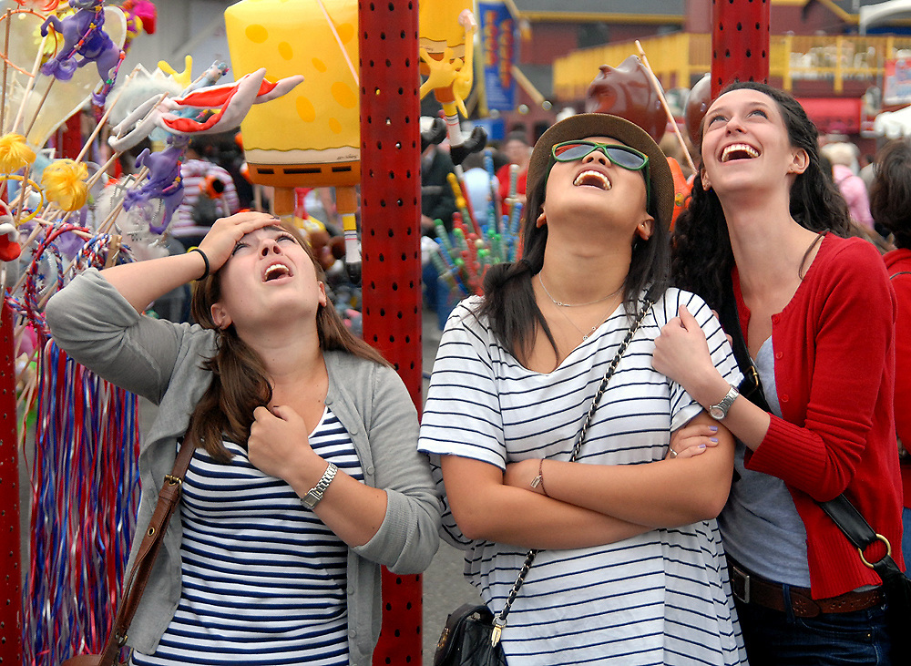 Friends take time out at the Puyallup fair to watch people riding the Extreme Scream ride, which goes up 20 stories in the air, before abruptly and quickly heading back to earth.