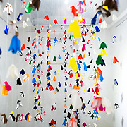 A small room full of hanging penguin origami pieces that forms part of an exhibit devoted to depictions of penguins in the Art Gallery wing at the Maritime Museum of Ushuaia. The museum is housed in the city's old prison.
