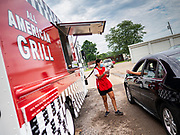"26 JUNE 2020 - DES MOINES, IOWA: NADINE GARCIA, a worker at the American Grill trailer, delivers corn dogs to a customer at Fair Food Friday in Des Moines. The 2020 Iowa State Fair, like many state fairs in the Midwest, has been cancelled this year because of the COVID-19 (Coronavirus) pandemic. The cancellation of the fair left many small vendors stranded with no income. Some of the fair food vendors in Iowa started ""Fair Food Fridays"" on a property a few miles south of the State Fairgrounds. People drive up and don't leave their cars while vendors bring them the usual midway fare; corndogs, fried tenderloin sandwiches, turkey legs, deep fried Oreos, lemonaide and smoothies. Fair Food Friday has been very successful. The vendors serve 450-500 people per Friday and during the lunch rush people wait in line in their cars 30 - 45 minutes to place an order.     PHOTO BY JACK KURTZ"