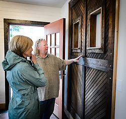 Joanne Waterman (right) talks about one of the historic doors of the restored fire hall on the grounds of historic Fort William H. Seward in Haines, Alaska with Susan Weerasinghe of Haines during a recent open house celebrating the completion of the fire hall restoration. The old door is used as a decorative element inside the fire hall.<br /> <br /> The fire hall was restored over a two-year period by owners Waterman and Phyllis Sage who also own the fort&rsquo;s original guardhouse, now a bed and breakfast, located next door to the fire hall.<br /> <br /> After being absent from the historic Fort Seward skyline since approximately the 1930s, the 60-foot tower of the fort&rsquo;s fire hall has been restored to its original height. The building and tower, built around 1904 in Haines, Alaska, was shortened to approximately half its height in the 1930s for unknown reasons. The restoration included rebuilding a missing 35-foot section of the 60-foot tower whose purpose was to dry fire hoses. The tower restoration was completed by building its four sections on the ground and then hoisting those sections with a crane into place on top of each other.<br /> <br /> Through the years, the historic Fort Seward area, a former U.S. Army post, has been referred to as Fort William H. Seward, Chilkoot Barracks, and Port Chilkoot. The National Historic Landmarks listing record for the fort says that &quot;Fort Seward was the last of 11 military posts established in Alaska during the territory's gold rushes between 1897 and 1904. Founded for the purpose of preserving law and order among the gold seekers, the fort also provided a U.S. military presence in Alaska during boundary disputes with Canada. The only active military post in Alaska between 1925 and 1940, the fort was closed at the end of World War II.&rdquo; <br /> <br /> The bottom portion of the fire hall is being leased as commercial space. Due to fire code restrictions there is no public access to the upper portion of the tower.