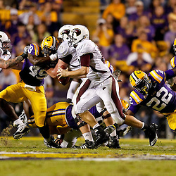 November 13, 2010; Baton Rouge, LA, USA; Louisiana Monroe Warhawks quarterback Kolton Browning (15) is pressured by LSU Tigers linebacker Ryan Baker (22) and defensive end Barkevious Mingo (49) during the first half at Tiger Stadium. LSU defeated Louisiana-Monroe 51-0.  Mandatory Credit: Derick E. Hingle