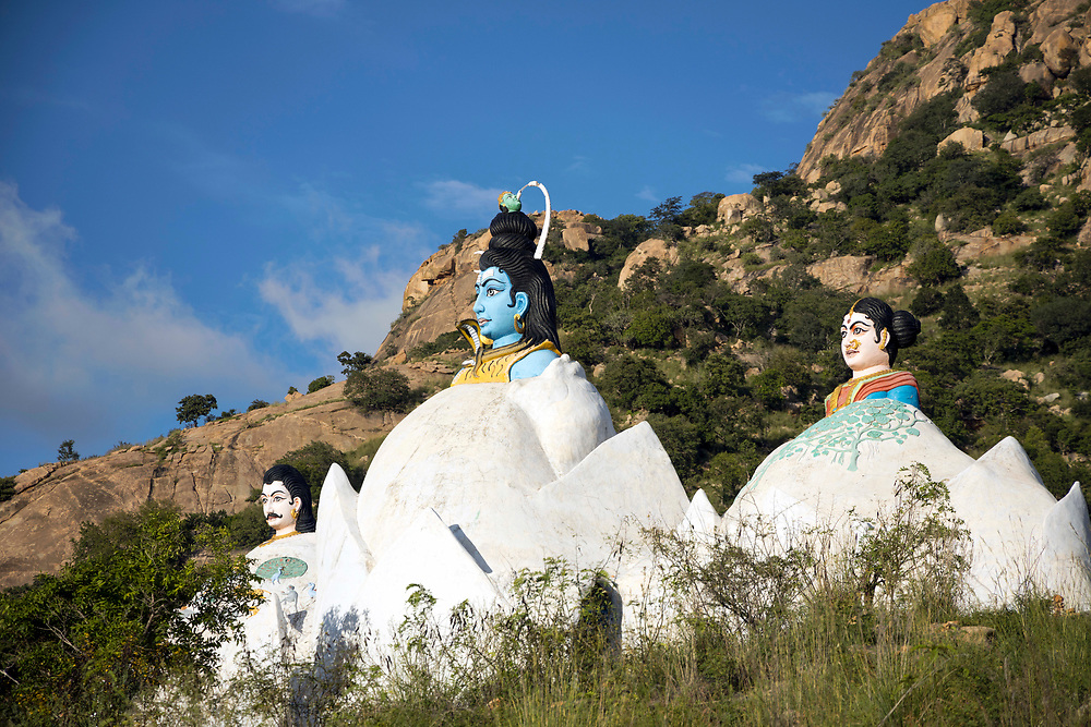 THIMMAMMA MARRIMANU, INDIA - 29th October 2019 - The white temple with statue icons of the goddess Thimmamma, her husband and Lord Shiva located on the mountain opposite the Thimmamma banyan tree in Andhra Pradesh, South India. The site's main entrance is said to be a place where Lord Shiva worshipped and performed penance rituals. Thimmamma Marrimanu is home to the world's largest single tree canopy.