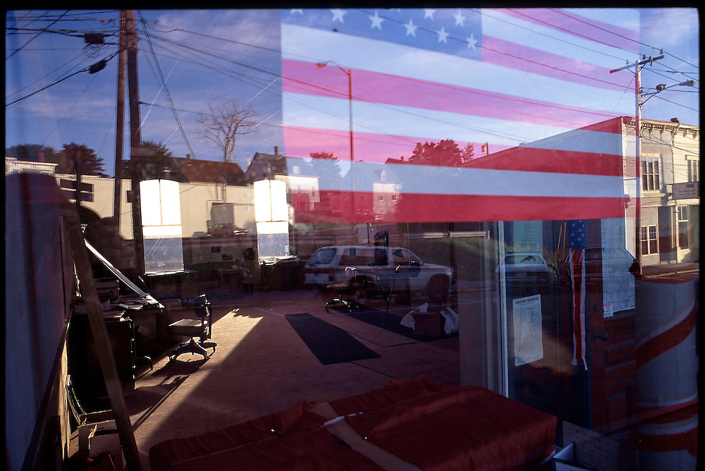 A flag hangs in the window of an empty store front in Eastport, Maine.